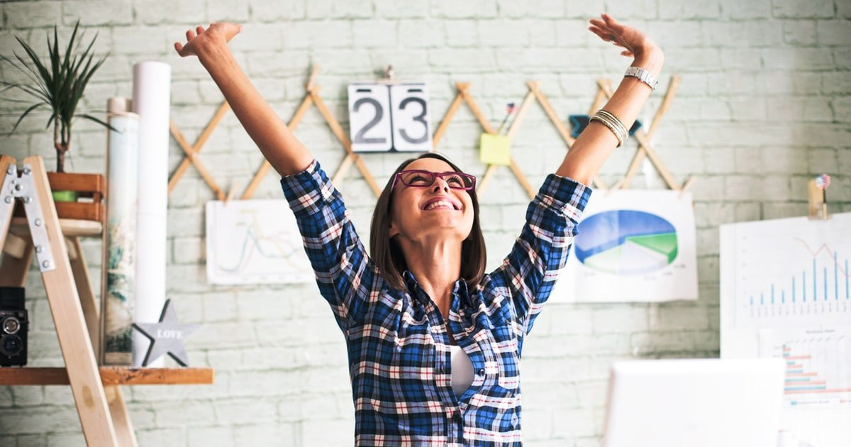 excited, young business woman celebrating success in the office with her arms up in the air